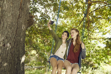 Two best friends sitting together on a swing taking selfie with smartphone - SRYF00496