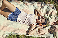 Young woman lying on blanket listening music with headphones - SRYF00499