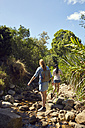 Back view of two young women walking in nature - SRYF00508