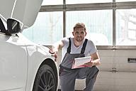 Car mechanic in a workshop examining car - LYF00685