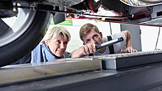 Car mechanic with client in workshop at car - LYF00688