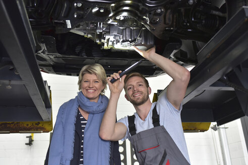 Portrait of smiling car mechanic with client in workshop at car - LYF00691