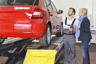 Car mechanic with client in workshop at car - LYF00694