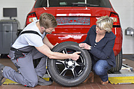 Car mechanic with client and tyre in workshop at car - LYF00697