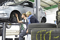 Car mechanic with client in workshop at car - LYF00700