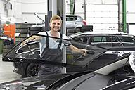 Car mechanic in a workshop changing car window - LYF00715