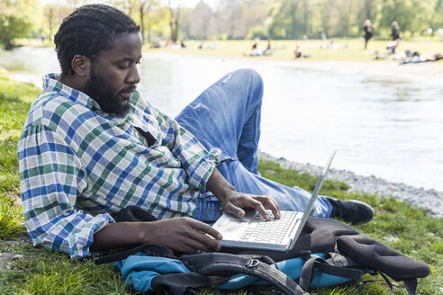 Man on a meadow using laptop - TCF05405