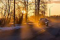 Car on road in winter at sunset - KNTF00844