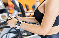 Woman in gym with smartwatch using an elliptical trainer - MGOF03269