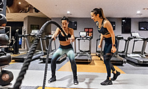Woman doing battle rope exercise at gym - MGOF03284