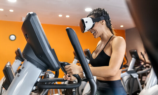 Woman wearing VR glasses on an elliptical traine in the gym - MGOF03293