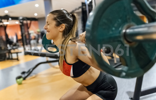Young woman lifting weight in gym - MGOF03311