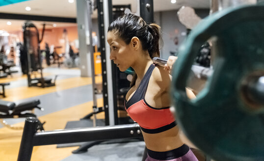 Woman lifting barbell in gym - MGOF03314