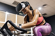 Woman with VR glasses on spinning bike in the gym - MGOF03329