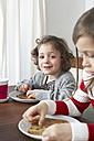 Portrait of smiling little girl at breakfast table - FSF00831