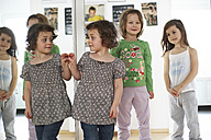 Little girl watching her mirror image while her friends standing in the background - FSF00846