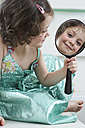 Mirror image of smiling little girl looking at hand mirror - FSF00849