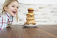 Portrait of smiling little girl with stack of baked goods - FSF00861