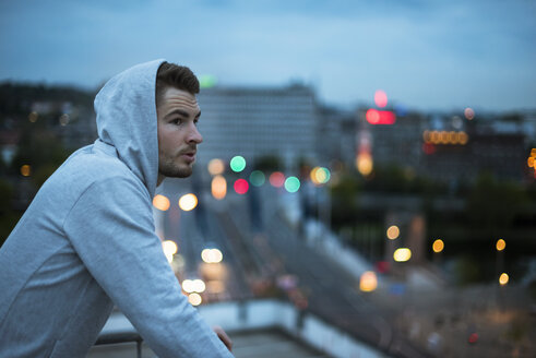 Athlete wearing hoodie above the city at dawn - DIGF02396
