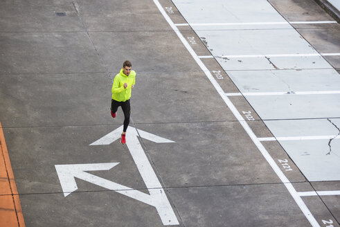 Young man running on parking level - DIGF02402