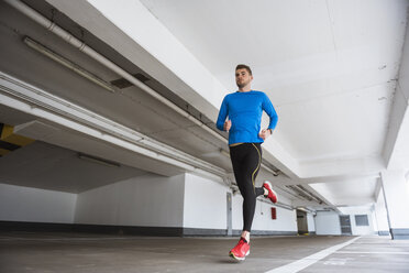 Young man running in a parking garage - DIGF02411