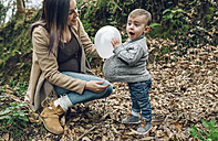Happy pregnant mother and little boy having fun with a balloon in forest - DAPF00728