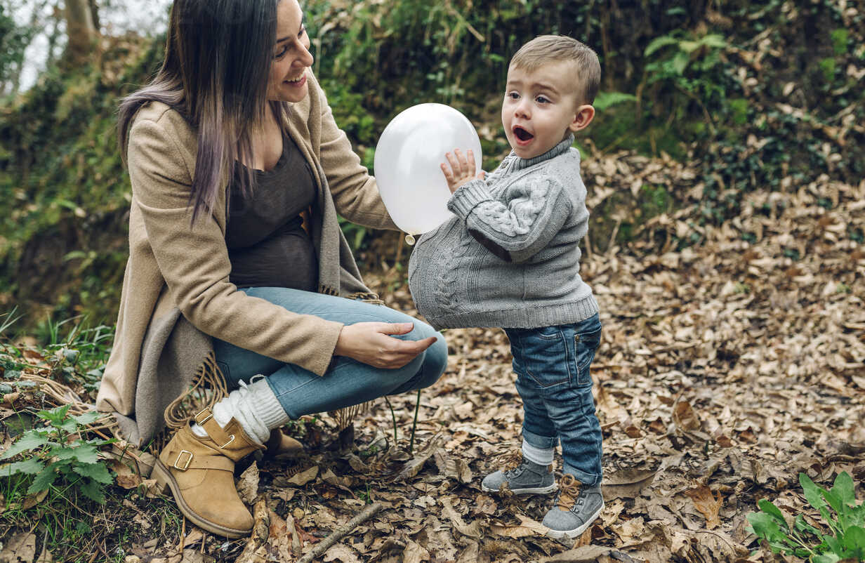 Happy pregnant mother and little boy having fun with a balloon in forest - DAPF00728 - David Pereiras/Westend61