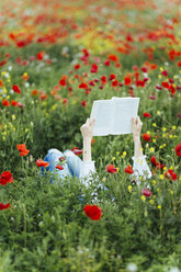 Woman lying in a field reading a book - JPF00188