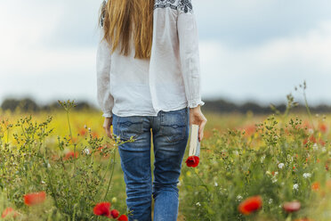 Woman walking in a flower field holding book - JPF00191