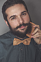 Man combing his beard with a wooden comb, wearing denim shirt and cork bow tie - RTBF00833