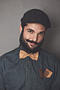 Portrait of bearded man wearing cap, denim shirt, cork bow tie, wearing wooden combs for beard and mustache in his pocket - RTBF00839