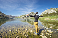 Spain, Asturias, Picos de Europa National Park, man standing with raised arms at Lakes of Covadonga - EPF00442