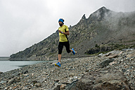Italy, Alagna, trail runner on the move at a lake near Monte Rosa mountain massif - ZOCF00273
