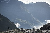 Italy, Alagna, trail runner on the move near Monte Rosa mountain massif - ZOCF00276