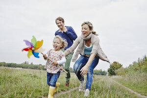 Family on a trip with daughter holding pinwheel - RORF00844