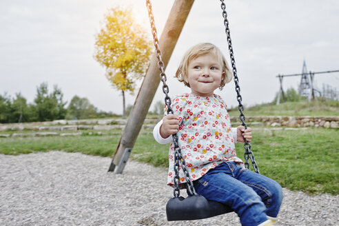 Smiling girl on swing on playground - RORF00847