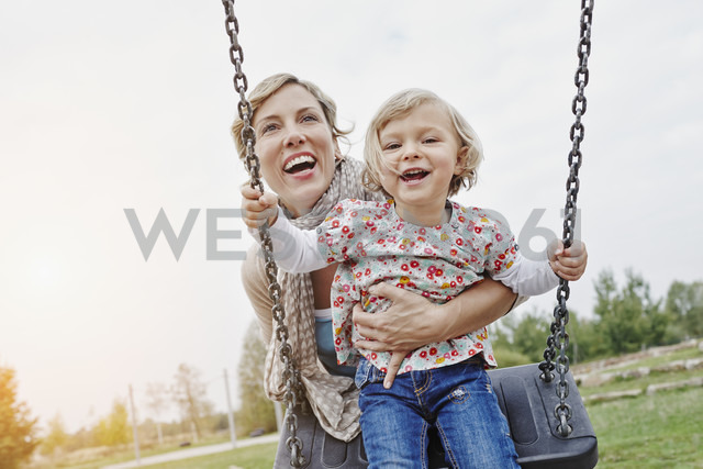 Mother with daughter on swing on playground - RORF00850 - Roger Richter/Westend61