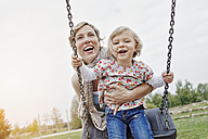 Mother with daughter on swing on playground - RORF00850