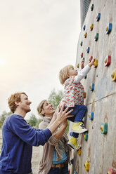 Girl climbing on a wall supported by parents - RORF00856