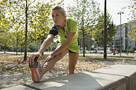 Female athlete stretching in urban park - ZOCF00280