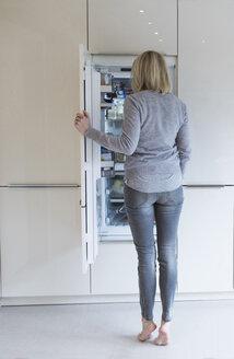 Woman looking into fridge - CHPF00398