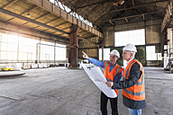 Two men with plan wearing safety vests talking in old industrial hall - DIGF02418