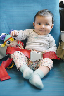 Happy baby girl sitting on a plane seat with a doll and the seat belt fastened - GEMF01605