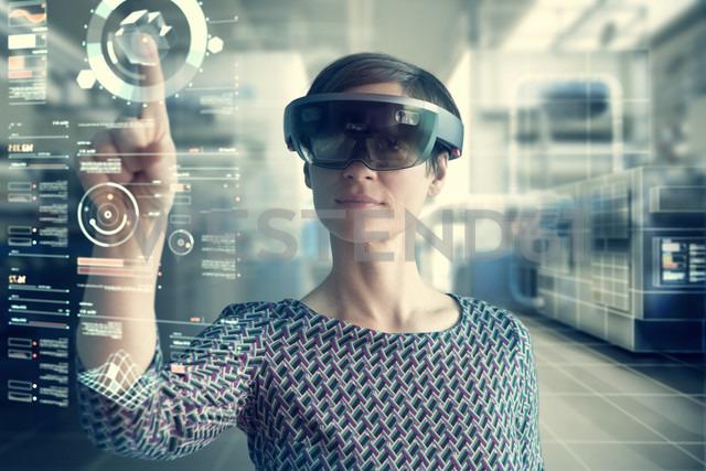 Woman wearing mixed reality smartglasses touching transparent screen - RBF05665 - Rainer Berg/Westend61