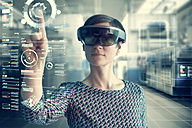Woman wearing mixed reality smartglasses touching transparent screen - RBF05665