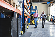 Two men walking in industrial hall looking at shelves - DIGF02431