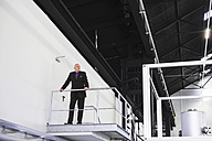 Businessman standing on platform overlooking industrial hall - DIGF02440