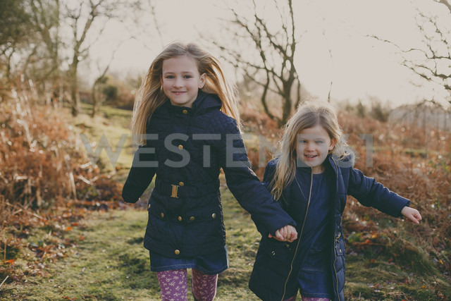 Two sisters running on a meadow together - NMSF00081