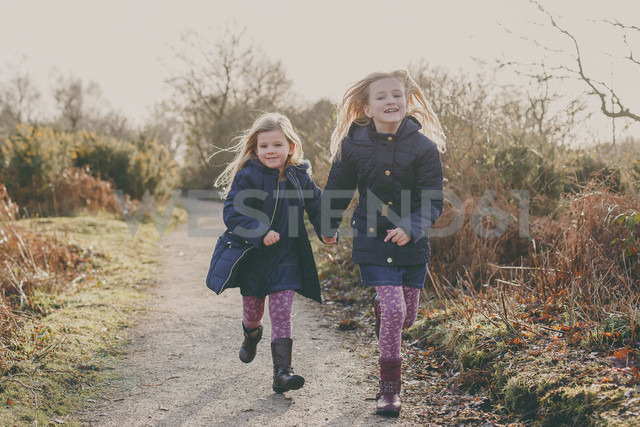 Two sisters running on a rural path together - NMSF00084