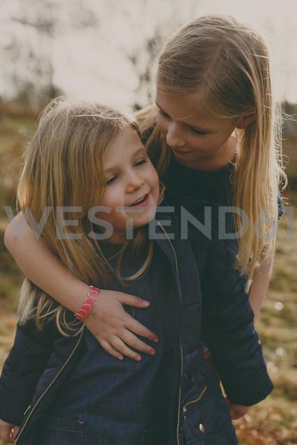 Girl hugging her sister outdoors - NMSF00099